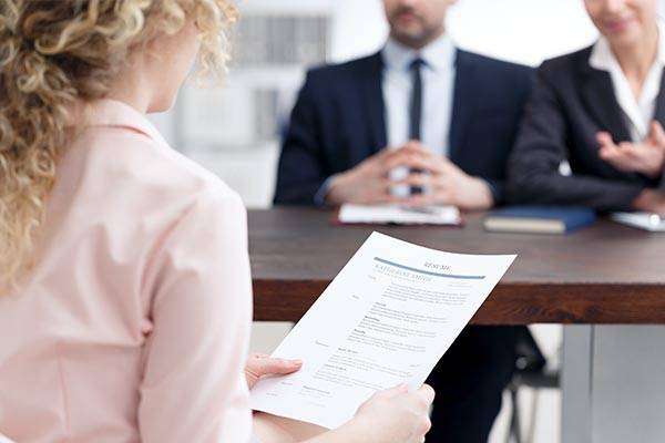 woman submitting resume to interviewers