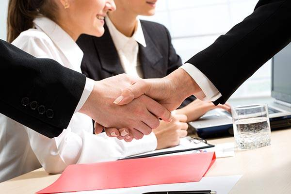 shaking hands while interviewers search